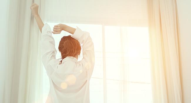 woman stretching, waking up to sunshine through window